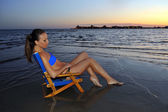 Woman sitting in the chair on the ocean shore — Stock Photo