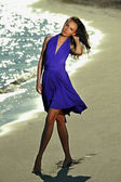 Model in dress walking on the beach — Stok fotoğraf