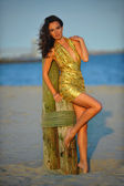 Model in golden dress on the beach — Stok fotoğraf