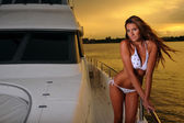 Seductive model posing on sailboat in sunset — Stock Photo