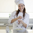 Beautiful girl cooking in the kitchen adding salt and pepper — Stock Photo #12450844