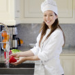 Young woman cleaning vegetable in the kitchen — Stock Photo #12450865