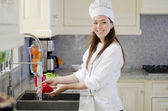 Young woman cleaning vegetable in the kitchen — Stockfoto