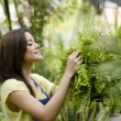 Cute female gardener arranging some plants for display — Stock Photo