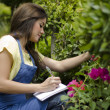 Cute female gardener doing inventory — Stock Photo