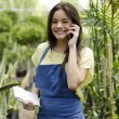 Cute female florist taking an order from a customer - Stock Photo