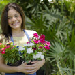 Portrait of cute smiling female gardener with flowerpots in garden — Stock Photo