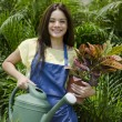 Cute young female gardener standing in orchard with flowerpot and watering can — Stock Photo