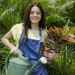 Cute young female gardener standing in orchard with flowerpot and watering can — Stock Photo #13107042
