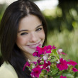 Young pretty woman smiling and holding flowers in a garden — Stock Photo