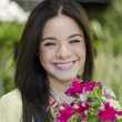 Cute happy girl smiling in a garden with flowers — Stock Photo #13107360