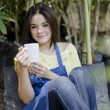 Young happy girl sitting in a garden with white cup — Stock Photo #13107366