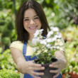 Closeup portrait of cute young girl with flowerpot smiling in orchard — Stock Photo #13107400