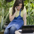 Young happy girl sitting in a garden with laptop while using her cellphone — Stock Photo