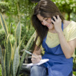 Young happy girl sitting in a garden while using her cellphone and making notes  — Photo
