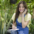 Young happy girl sitting in a garden while using her cellphone and making notes - Stock Photo