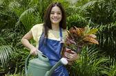 Söt ung kvinnlig trädgårdsmästare står i fruktträdgård med blomkruka och vattning kan — Stockfoto