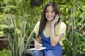Young happy girl sitting in a garden while using her cellphone and making notes — Stock Photo