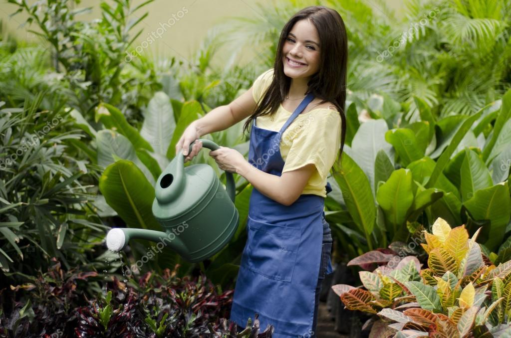 Joven mujer jardinero regando las plantas fotos de stock for Se necesita jardinero