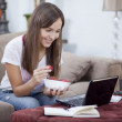 Woman on sofa using a laptop while having strawberries — Stock Photo
