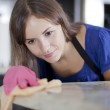 Happy young housewife in pink gloves cleaning a glass table in the kitchen — Stock Photo