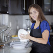 Gorgeous happy woman in black apron washing dishes in the kitchen — Stock Photo
