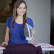 Happy young woman ironing on ironing board at home, smiling. — Stock Photo