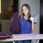 mulher jovem feliz engomadoria na tábua de passar em casa, sorrindo — Foto Stock