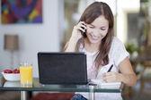 χαμογελώντας όμορφη γυναίκα με φορητό υπολογιστή, μιλώντας στο κινητό και γραπτώς το τετράδιό — Φωτογραφία Αρχείου