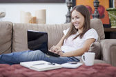 Woman relaxed on couch with laptop computer, coffee cup, pen and notebook — Stock Photo
