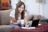 Joven muy sonriente sentada por laptop hacer anotaciones en su diario y tomando una taza de té — Foto de Stock