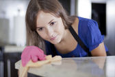 Happy young housewife in pink gloves cleaning a glass table in the kitchen — Stockfoto