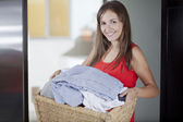 Smiling housewife holding full basket of laundry — Stock Photo