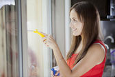 Portrait of attractive young woman cleaning window — Stock Photo