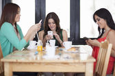 Young women centered around cell phones — Stock Photo