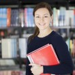 Smiling young woman at the library — Stock Photo #16627425