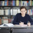 Young woman studying at the library — Stockfoto