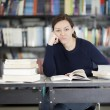 Bored young woman studying at the library — Stock Photo