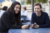 Smiling girls with mobile phones — Stock Photo