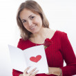 Smiling beautiful young woman holding a valentine's day postcard with heart — Stock Photo #18194503