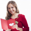 Smiling beautiful young woman holding a valentine's day postcard with heart — Stock Photo #18194505