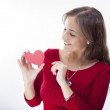 Stock Photo: Cute young woman holds a heart symbol