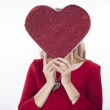 Cute young woman holds a heart symbol — Stock Photo