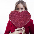Cute young woman holds a heart symbol — Stock Photo #18194769