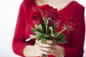 Woman in red sweater holding a rose — Stock Photo
