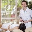 Therapist making a hot stones massage to his patient - Stock Photo