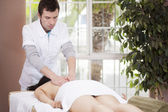 Handsome therapist makes massage to his patient — Stock Photo