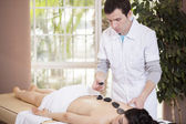 Therapist making a hot stones massage to his patient — Stock Photo