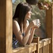 Girl drinking tea on veranda — Stock Photo