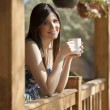Girl drinking tea on veranda — Stock Photo #22156411